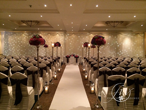 Mount Wolseley Civil Ceremony decor - spandx chair covers, purple bows, floral aisle stands and fairylight backdrop