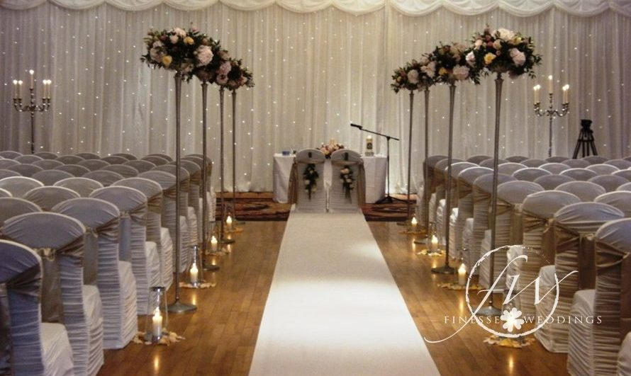 Civil ceremony decorations - fairylight backdrop, floral aisle stands, spandex chair covers with champagne bows and lanterns