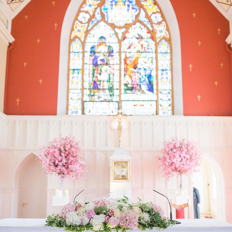 Pink cherry blossoms and alter arrangement for church wedding