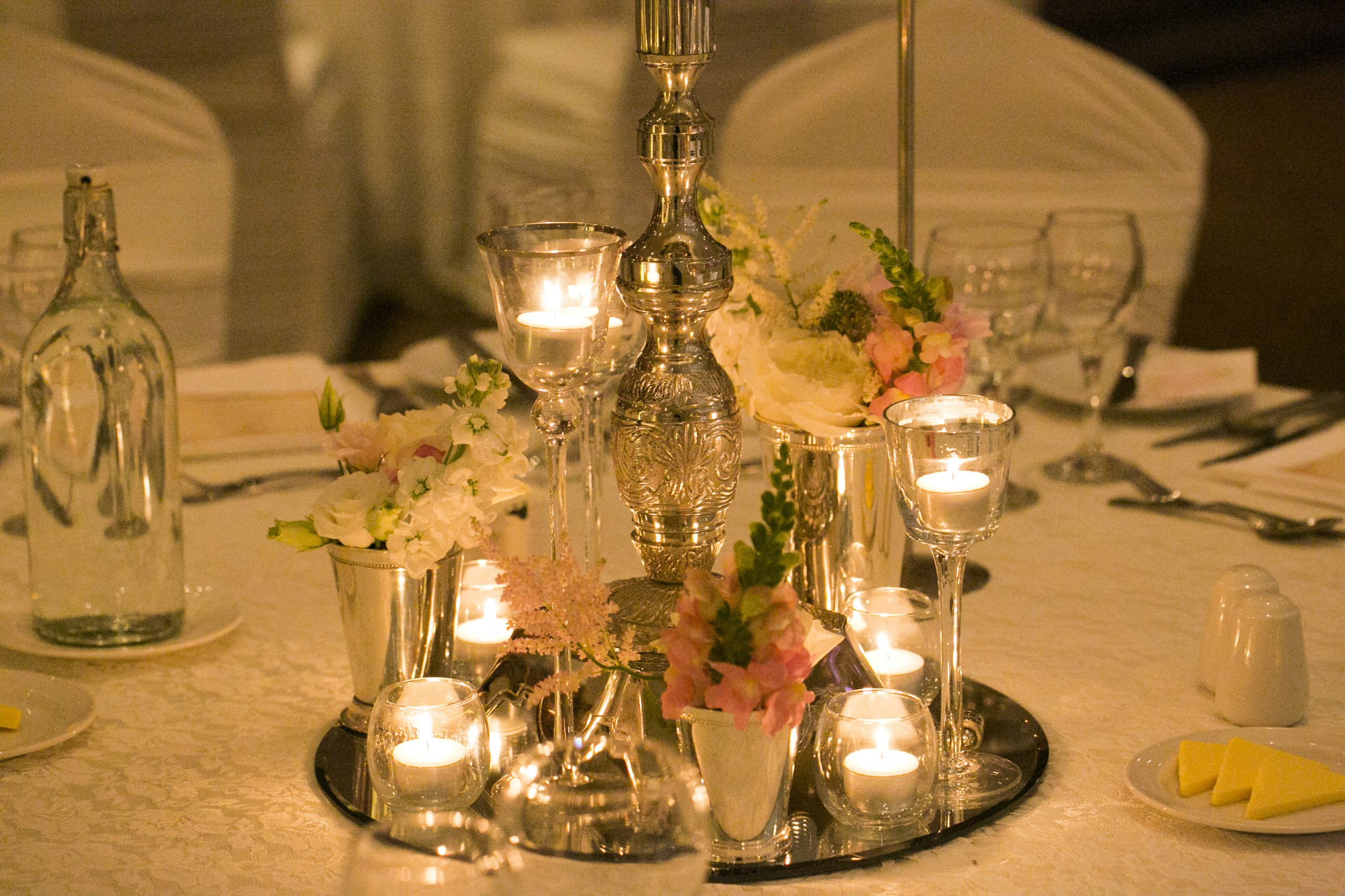 Wedding centerpiece surrounded by floral trickets and high tealights