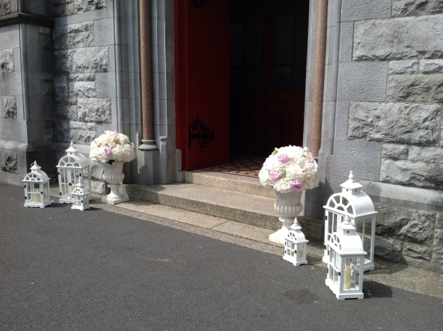 Floral urns and lanterns at church door
