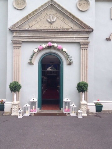 Wedding decorations - Flower arch, bay trees and lanterns at church door
