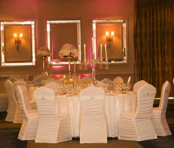 Full wedding table decoration - lace table overlays, spandex chair covers with diamante brooch, solid glass candelabra, silver single stemmed floral centerpiece
