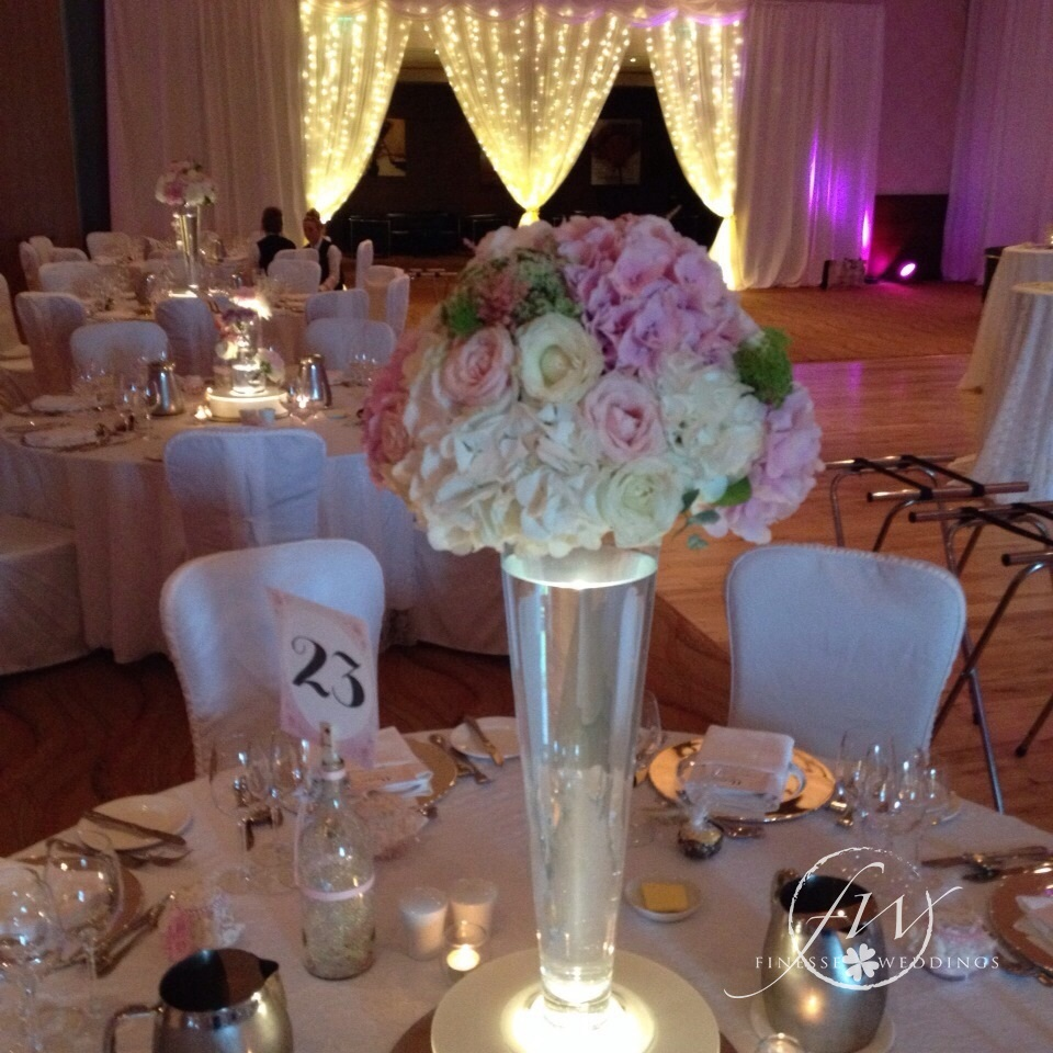 Fairylight door draping with rose and hydrangea floral centerpieces
