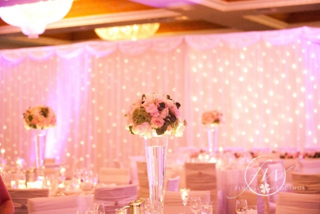 Heritage hotel - fairylight backdrop, pink uplighting and floral vase centerpieces