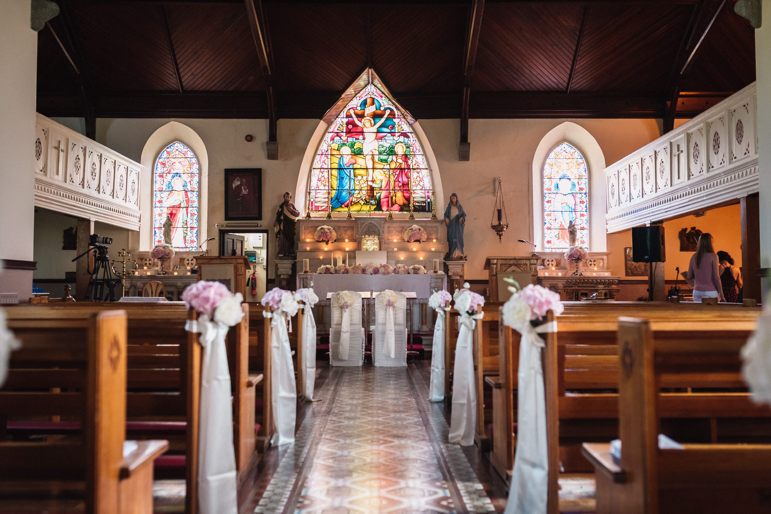 Church decorations - pew ends, bride and groom chairs and floral arrangements