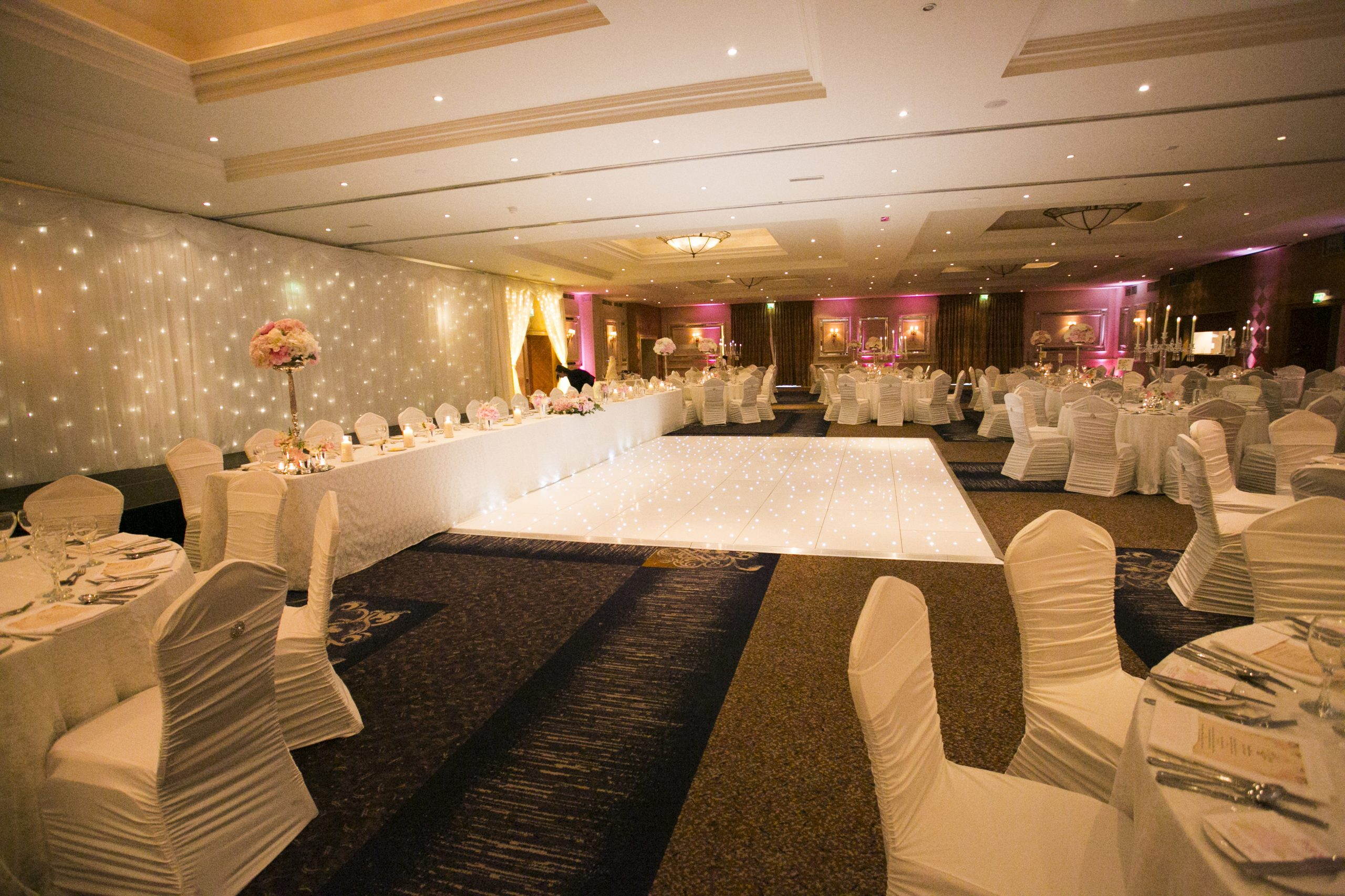 Mount Wolseley full room decor - fairylight backdrop, uplighting, door drapes, spandex chair covers with diamante brooches and centerpieces
