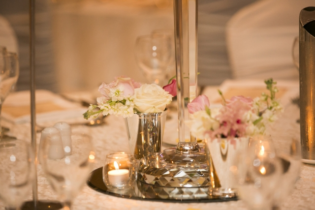 Silver floral trickets at base of glass candelabra
