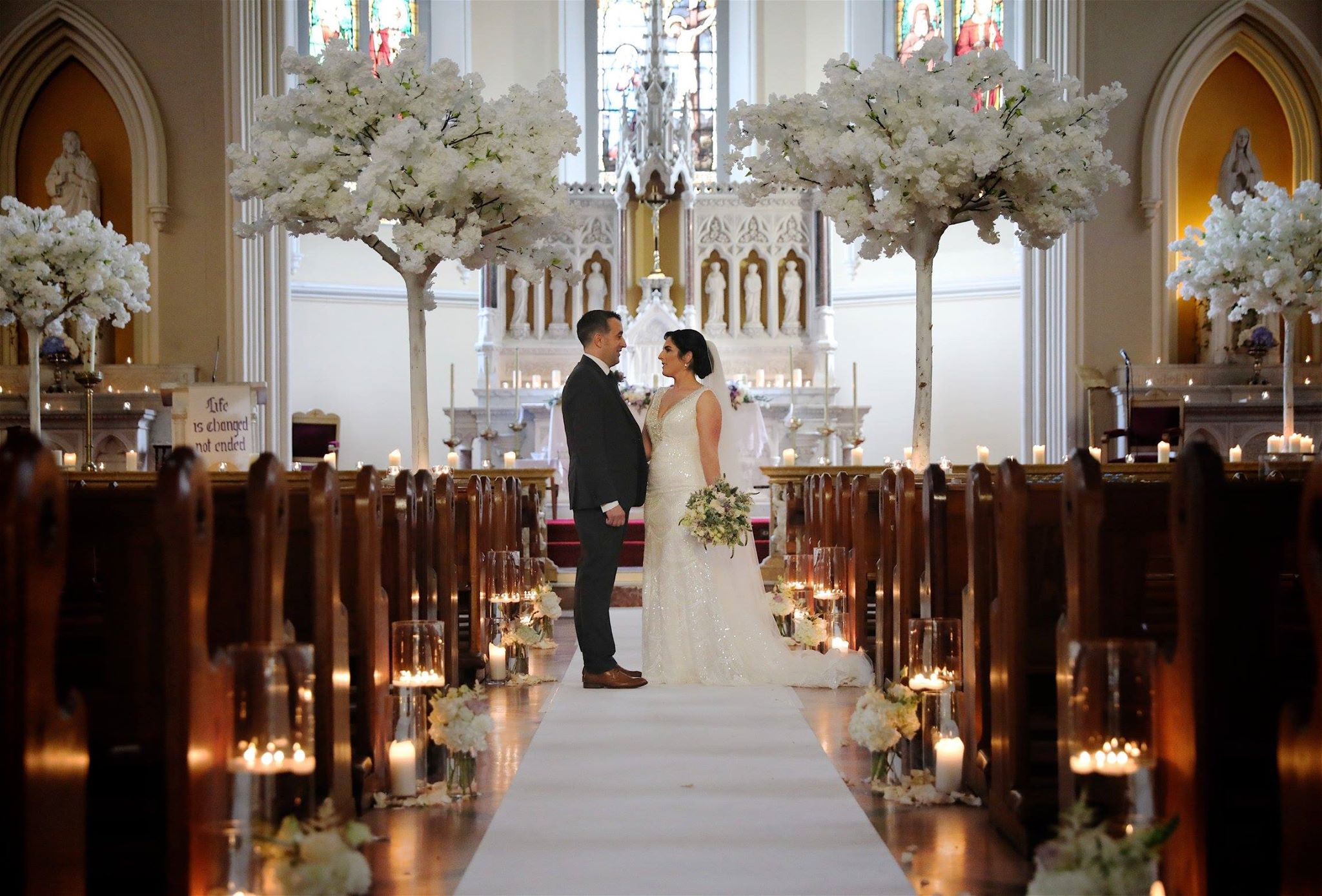 Romantic candle-lit church wedding set up , white cherry blossoms, candle vases, wedding flowers