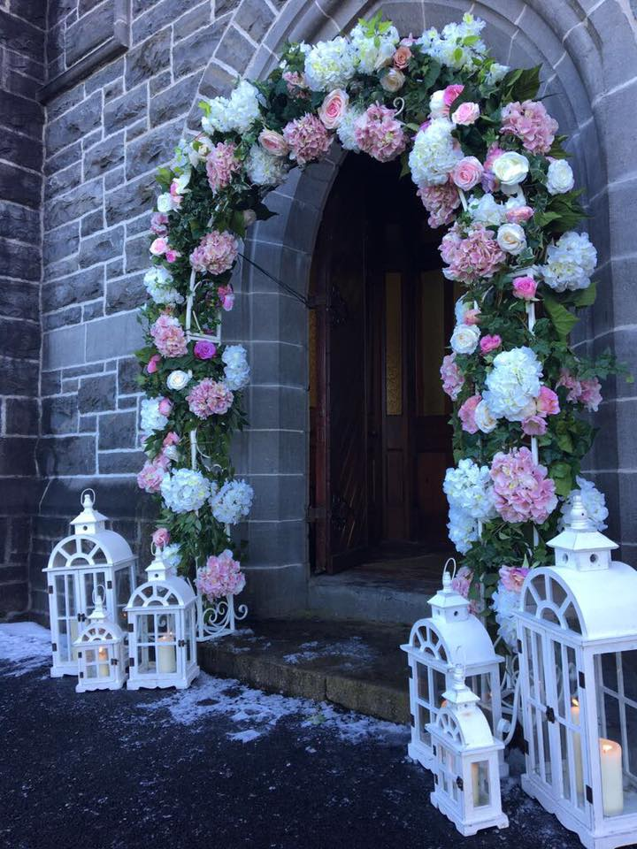 Floral arch and white lanterns for church wedding