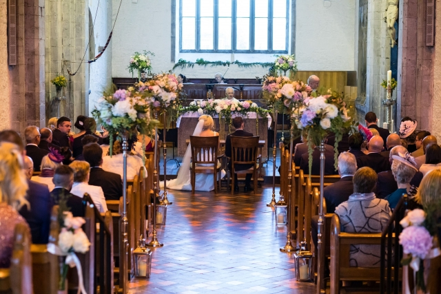 Floral decor and storm lanterns for church wedding